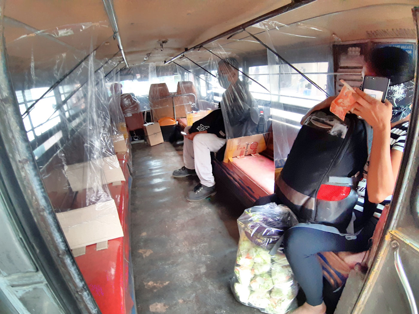 DIVIDERS. A jeepney in Trancoville, Baguio City puts up plastic covers to divide passengers. Photo by Mau Victa/Rappler