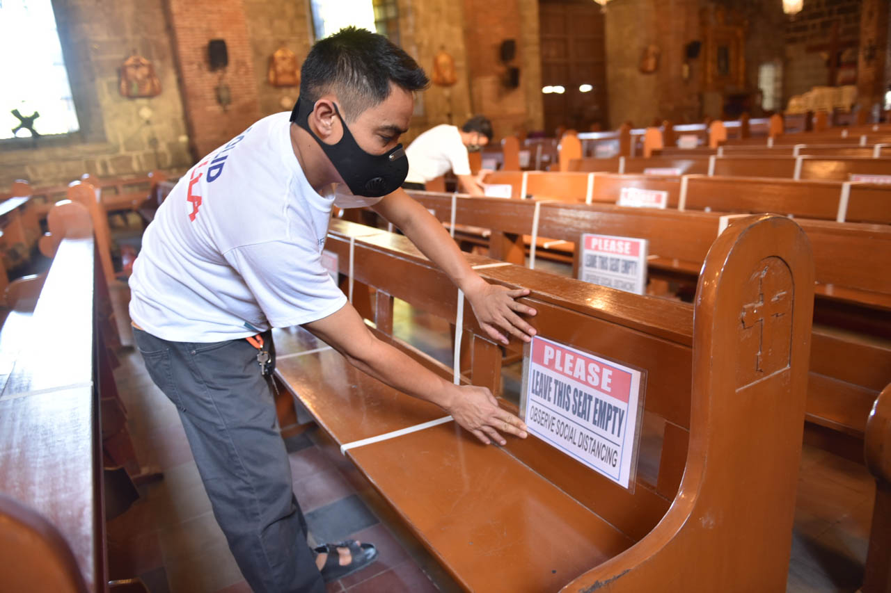 SAFE REOPENING. An altar server in a Cavite church puts physical distancing markers on June 9, 2020, as the place of worship is about to be opened to the public after 3 months of quarantine. Photo by Dennis Caparas Abrina/Rappler